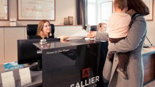 Sallier Immobilien Office Empfang Frau mit Kind erhält Dokumente von Mitarbeiterin