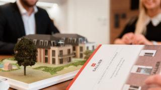 Mitarbeiter von Sallier Immobilien erklären Broschüre Vermietung von Wohnraum für Eigentümer & Verwalter