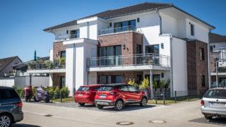 Sallier Immobilien Haus mit Eigentumswohnungen rote Autos vor der Tür Roydorfer Weg