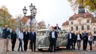 Teamfoto mit den Mitarbeitern von Sallier Immobilien auf dem Lüneburger Marktplat vor einem VW Bulli mit Sallier