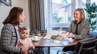 Sallier Immobilien Prokurist zeigt Frau im Prospekt Neubau Haus zum Kauf
