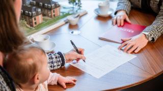 Frau unterschreibt Kaufvertrag Haus mit Immobilienkauffrau bei Sallier Immobilien